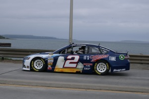 "Brad Keselowski waves to fans as he finishes his trip across the ""Mighty Mac"".  Historical Mackinac Island can be seen in the distance."