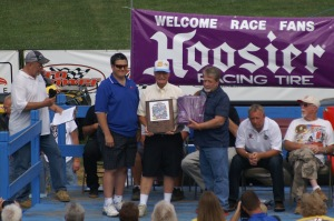 Allan E. Brown is presented with his plaque and Hoosier jacket on stage at Florence Speedway during his induction into the National Dirt Late Model Hall of Fame